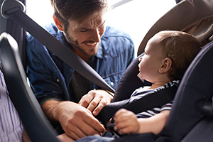 dad fitting baby into car seat