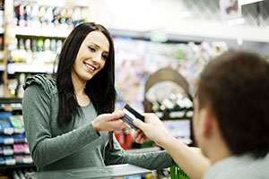 brunette brunette woman paying for goods at corner shop with credit card