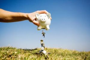 White piggy bank being emptied of coins onto a grass mound