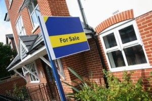 house with blue and yellow for sale sign in front garden