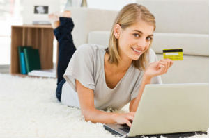 Smiling young woman with a laptop and a credit card