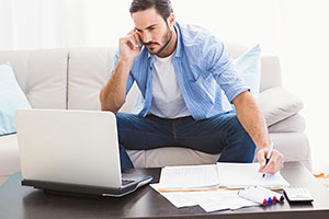 Man on laptop and phone sorting out energy bills