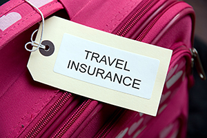 Luggage label with the words 'travel insurance' on a suitcase