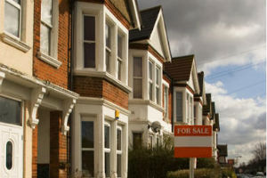Row of terraced properties with for sale sign