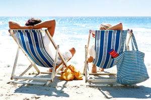 Two people sitting in deckchairs on a beach