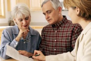 financial adviser speaking to elderly couple