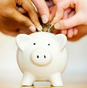Hands putting coins into a piggy bank
