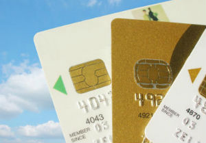 Gold credit card in between two white credit cards