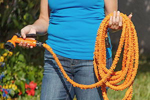 Woman holding an expandable hose