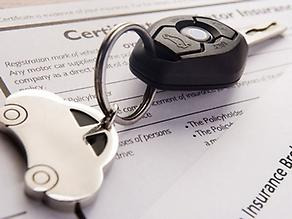car key sitting on top of insurance form