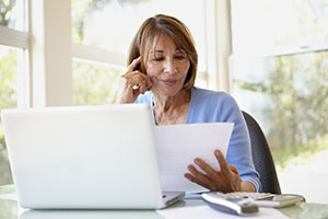 Woman in front of a laptop reading a document