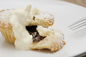 Mince pies on a plate with cream and a fork