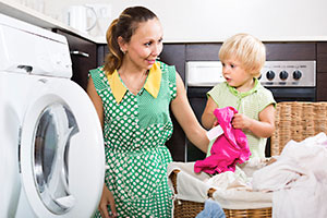 Mother and son washing clothes in a washing machine