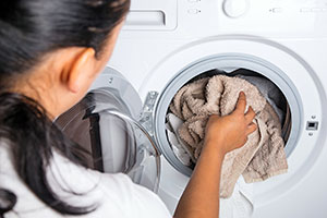 Washing machine being loaded with sheets by a woman