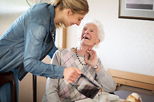 Older person sitting on a sofa and talking to her carer celebrating Carers Week