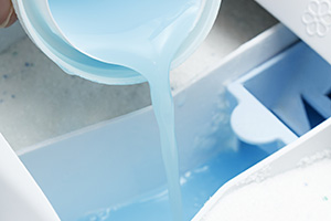 Pouring laundry liquid into the detergent drawer
