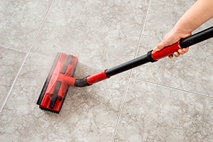 Cleaning the floor with a red and black steam mop