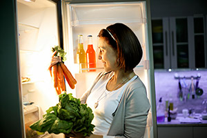 Picture of a woman loading a fridge freezer with fresh vegetables