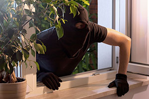 Burglar climbing through window