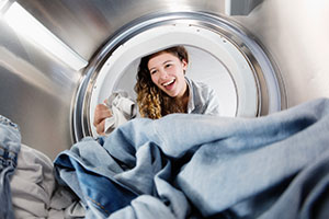 Woman looking into the drum of a tumble dryer