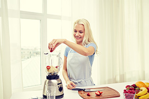 A woman using a blender in the kitchen.