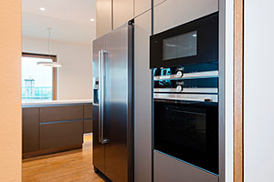 A picture of a sleek fridge, built in to a cupboard in the kitchen.