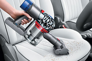 Dyson V8 cleaning a car