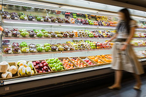 Woman walking past vegetables in supermarket