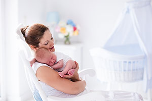 Mum and baby sleeping in white nursery