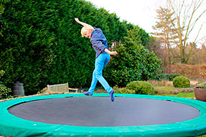 Trampoline in garden with child jumping