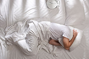 A man struggling to sleep in bed