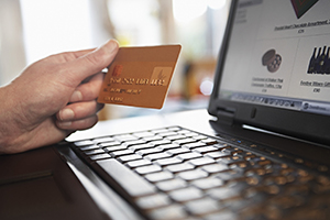 Shopper holding credit card over laptop