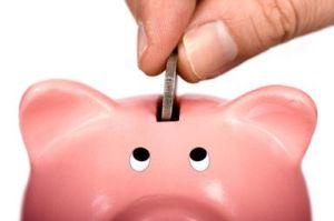 Coin being put into a piggy bank