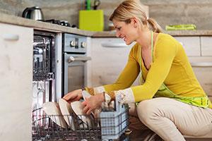 Woman loading a slimline dishwasher