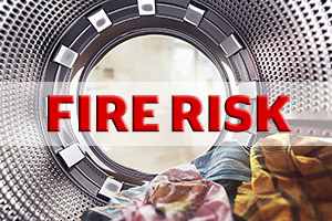 A tumble dryer drum with the words Fire Risk