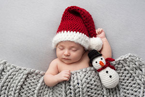 Newborn baby in santa hat with snowman