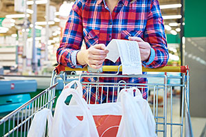 Woman with shopping list and trolley in supermarket