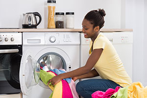 Woman emptying a tumble dryer of brightly coloured clothes