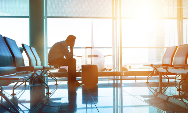 Man sits down in waiting area in airport terminal. He is ready for take off and looks out of the window at a plane. A suitcase stands before him.