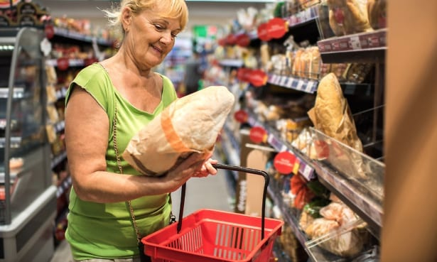 Woman buys bread in convenience supermarket