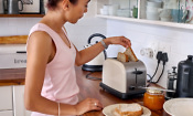 Woman making toast in a cream toaster, with a matching kettle in the kitchen