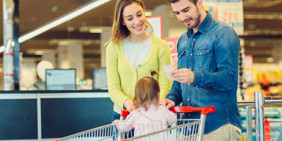 Couple with a baby shopping in a supermarket