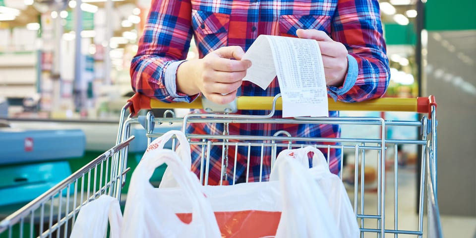 Man shopping in a supermarket with a trolley and receipt