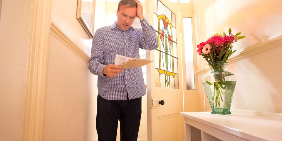 Man holding energy bill and looking worried
