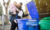 Father and child taking out plastic bottle for recycling