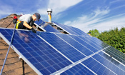Man installing solar PV panels on a roof
