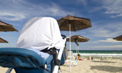 pushchair covered with sheet on beach