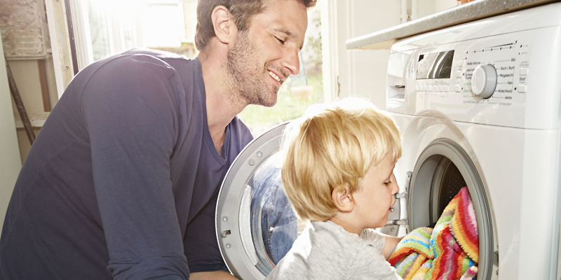 Dad and son loading clothes into a washer-dryer