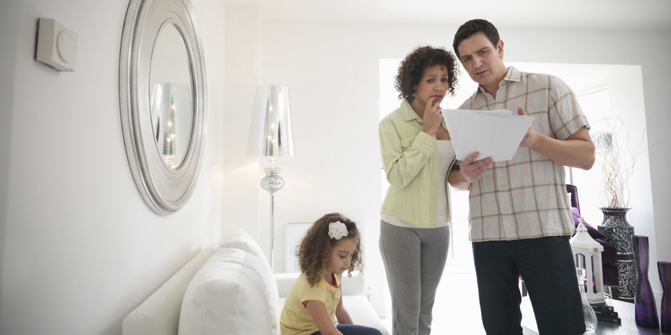 Couple discusses energy bill while child is on sofa