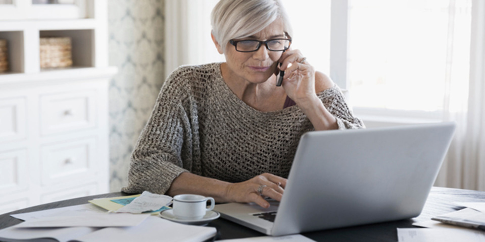 Woman on phone and using laptop for customer service
